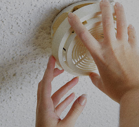 A hand adjusts a smoke detector on the ceiling