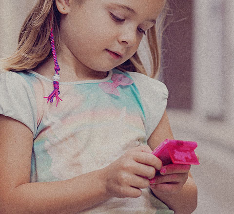 A girl plays with a small electronic device